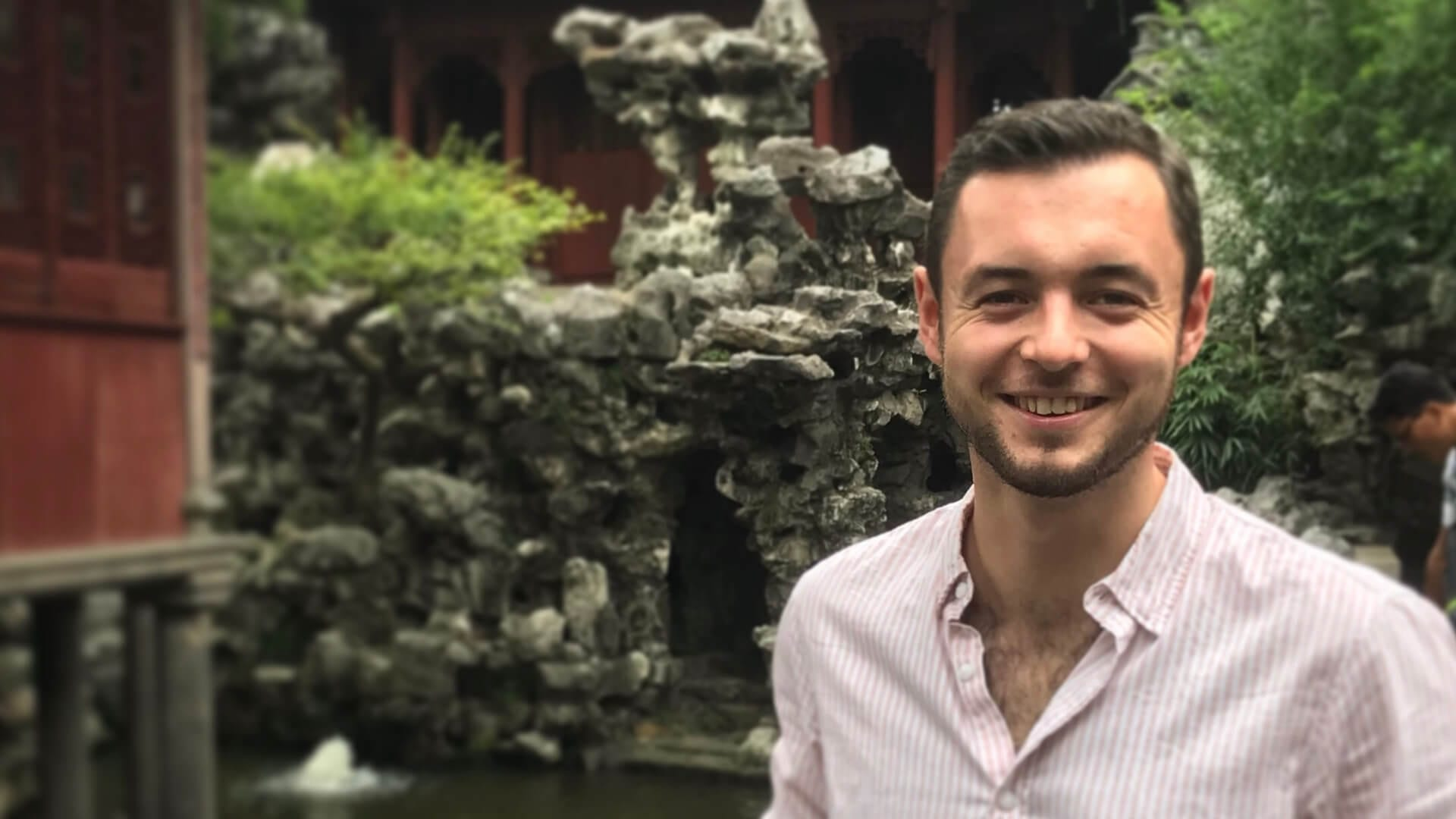 A young man is smiling and standing in front of a Chinese building in Shanghai.