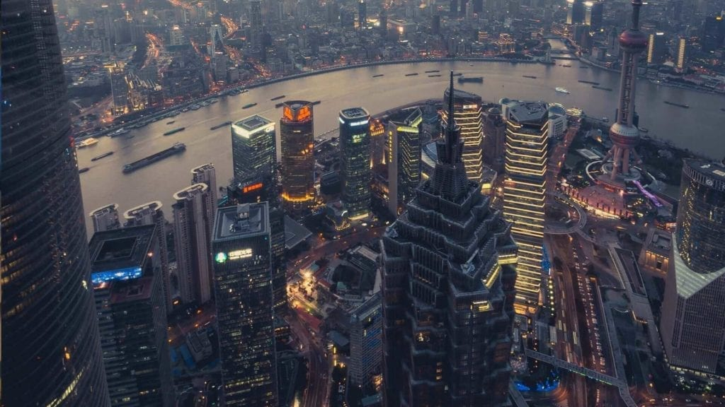 Areal view of illuminated high buildings next to a river during an evening in Shanghai.