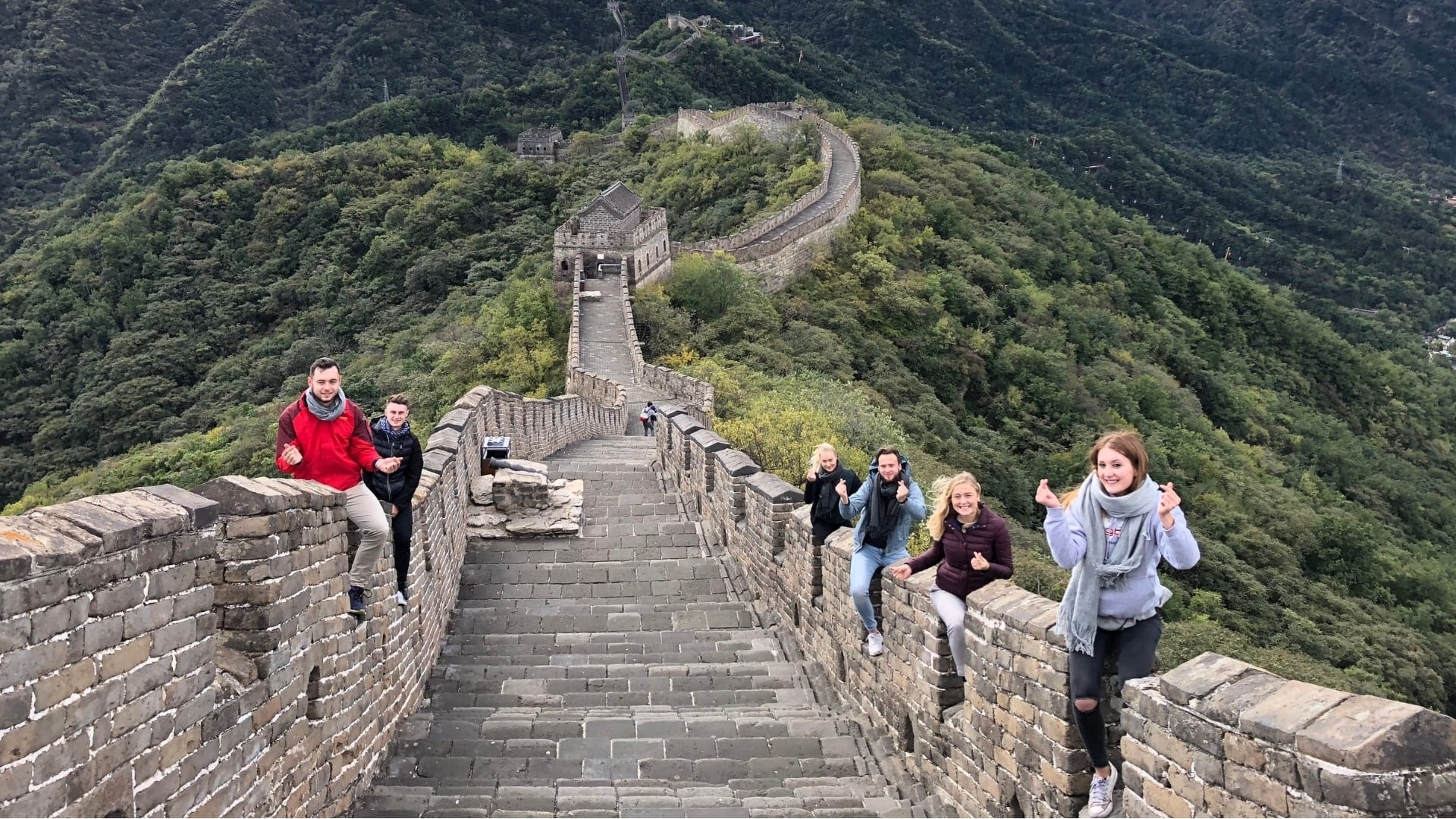 Students are sitting on a stone wall that goes over mountains in China.