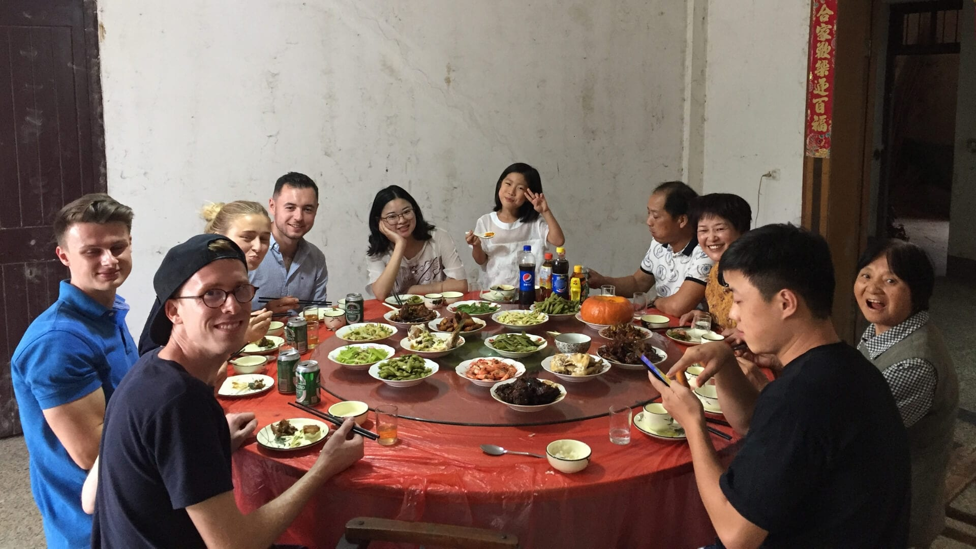 People are eating Chinese food on a round table in Shanghai.