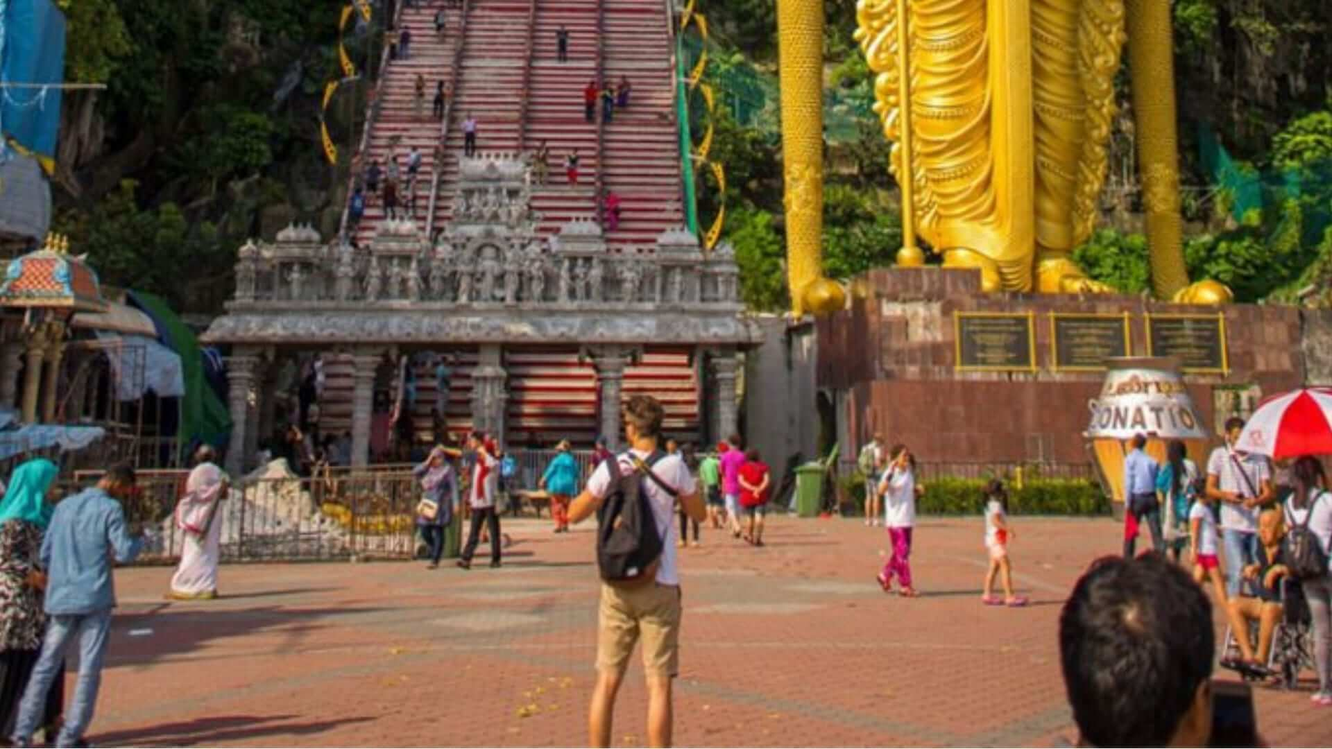 A boy is standing on a square with his head towards a big staircase that is leading to a temple in Malaysia.