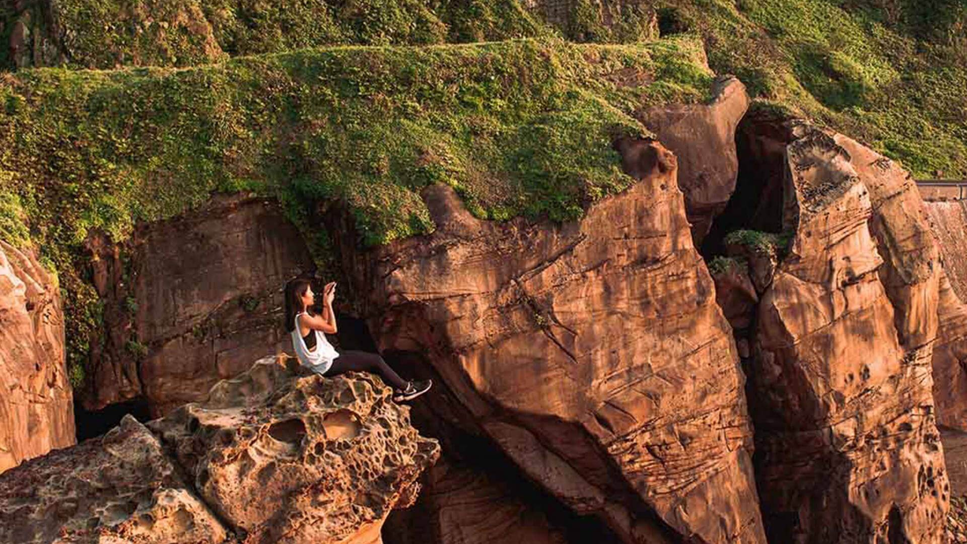 Girl sitting on the edge of a cliff and taking photos of the view.