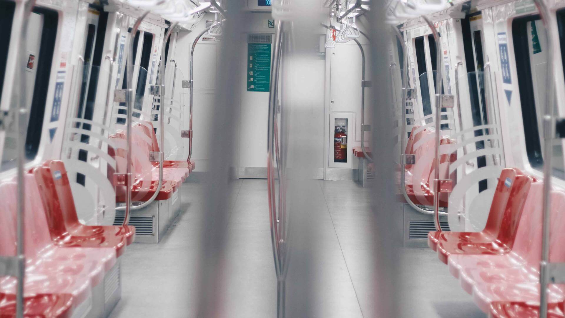 Inside of a metro train with white walls and red chairs.
