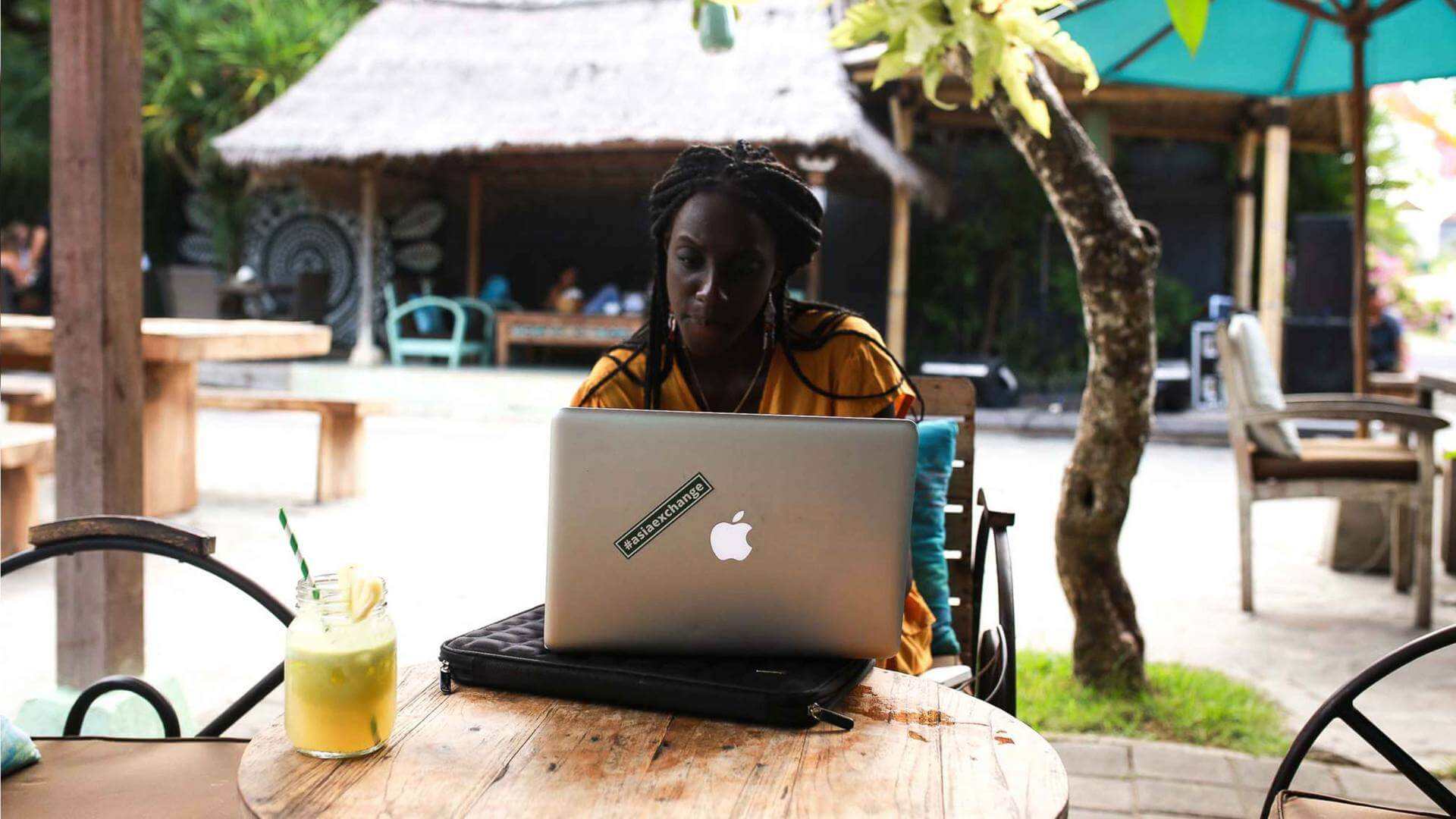 A girl is sitting down outside with her laptop a orange juice on a table in Bali.