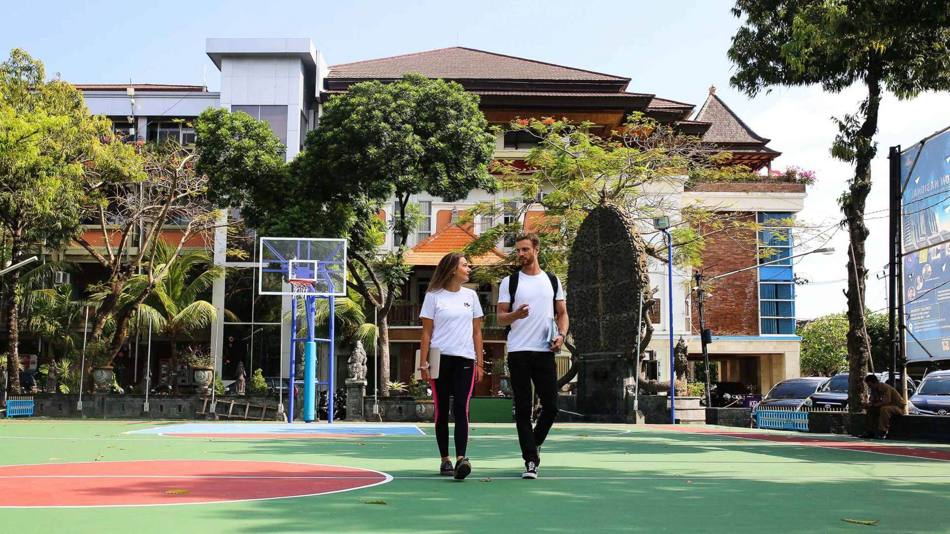 Two people walking on a basketball field with a big building in the background