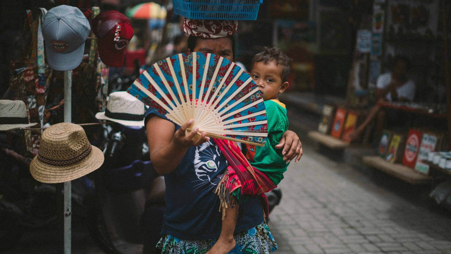 A woman is holding her son with one hand and a fan in the other