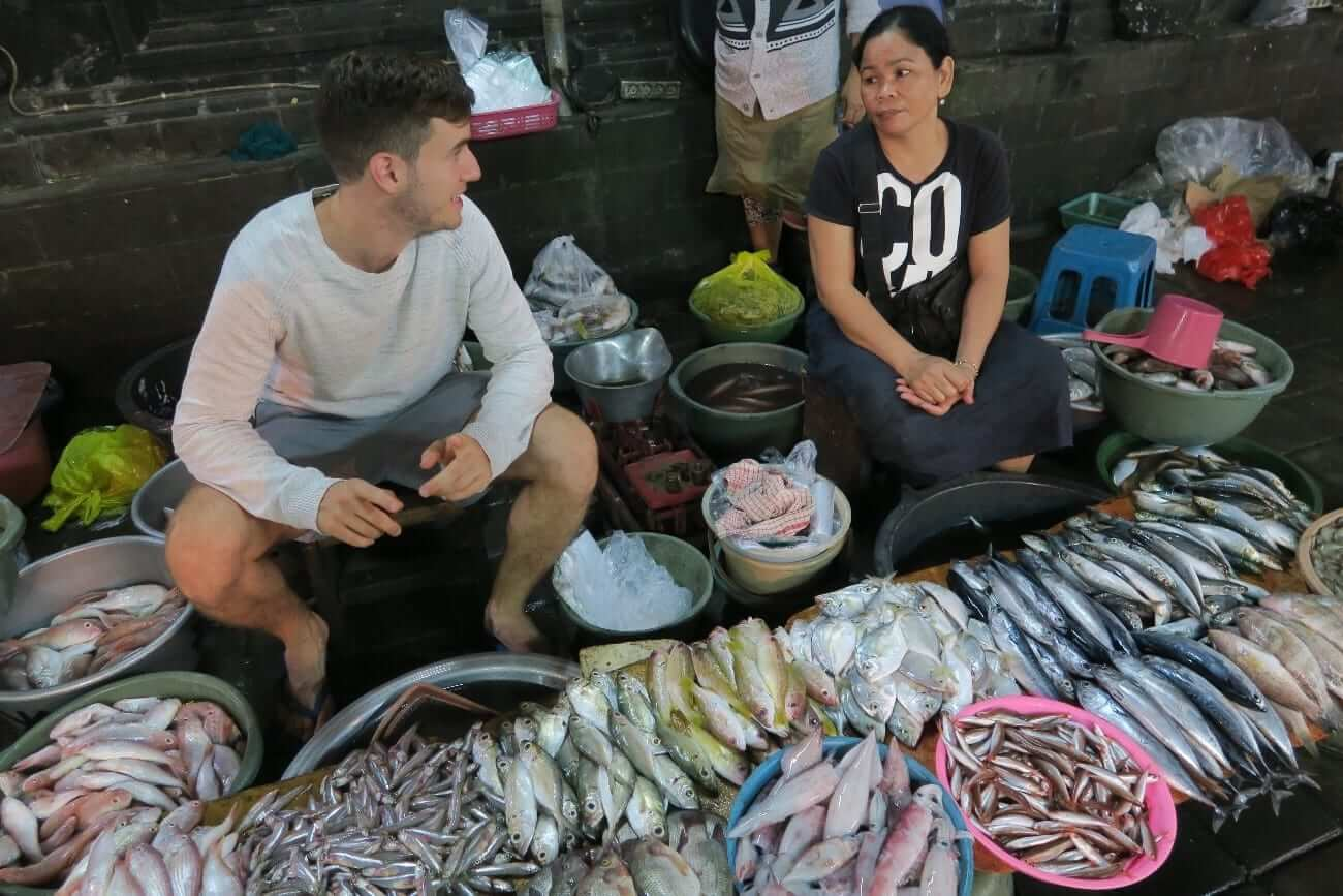 A caucasian boy and a south east asian fishmonger chatting