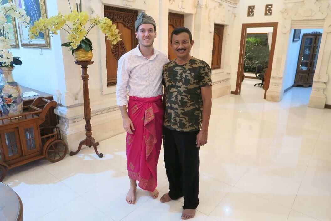 A young caucasian man poses for a photo with an Indonesian local