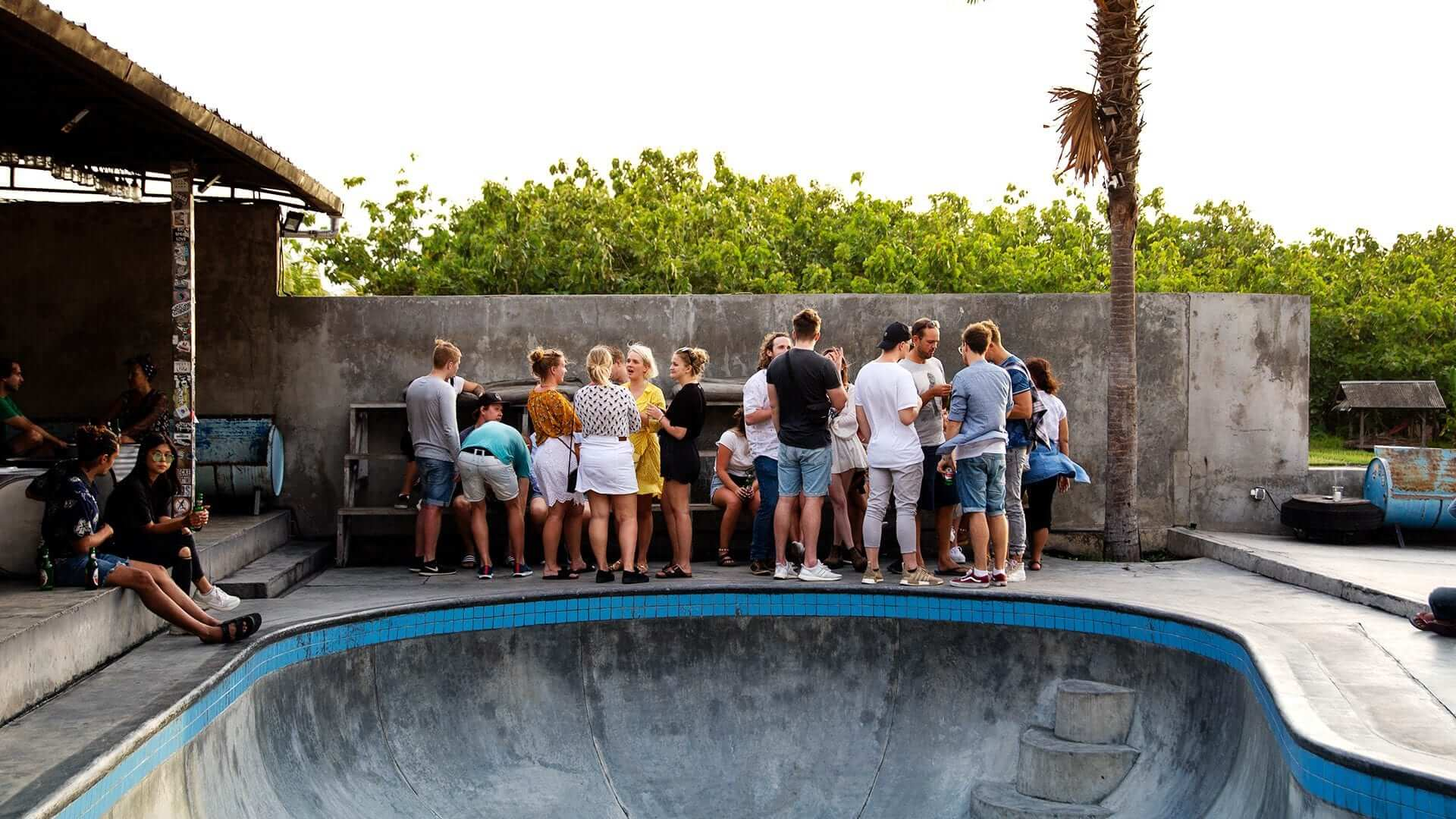 People standing around talking hanging out beside an empty pool
