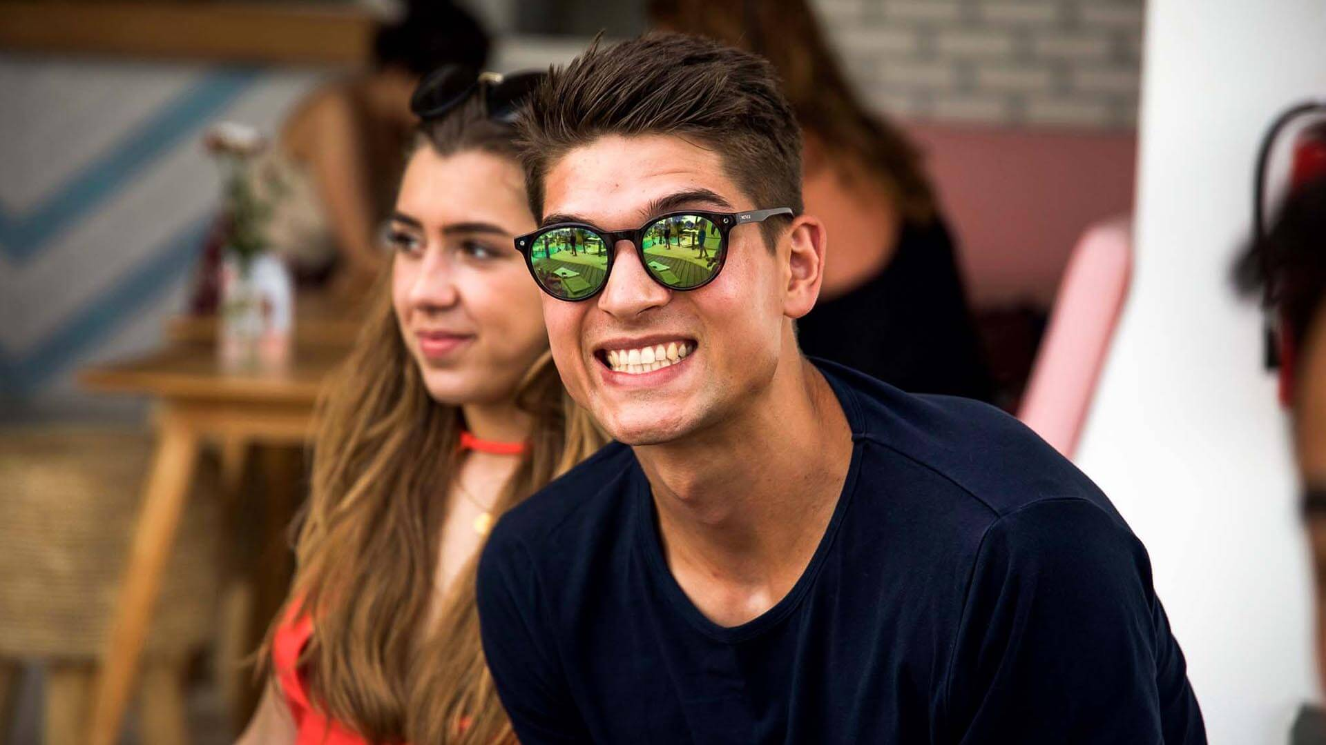 A man is smiling and wearing sunglasses
