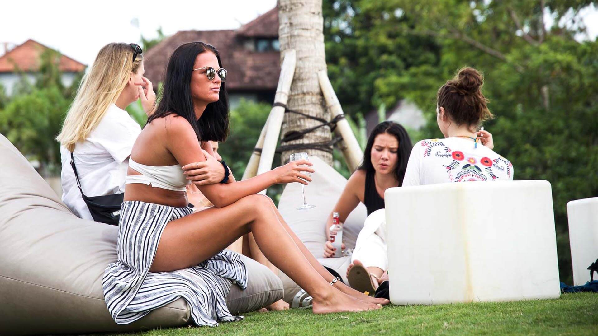 A group of girls sit on bean bags with a glass of drink in their hands