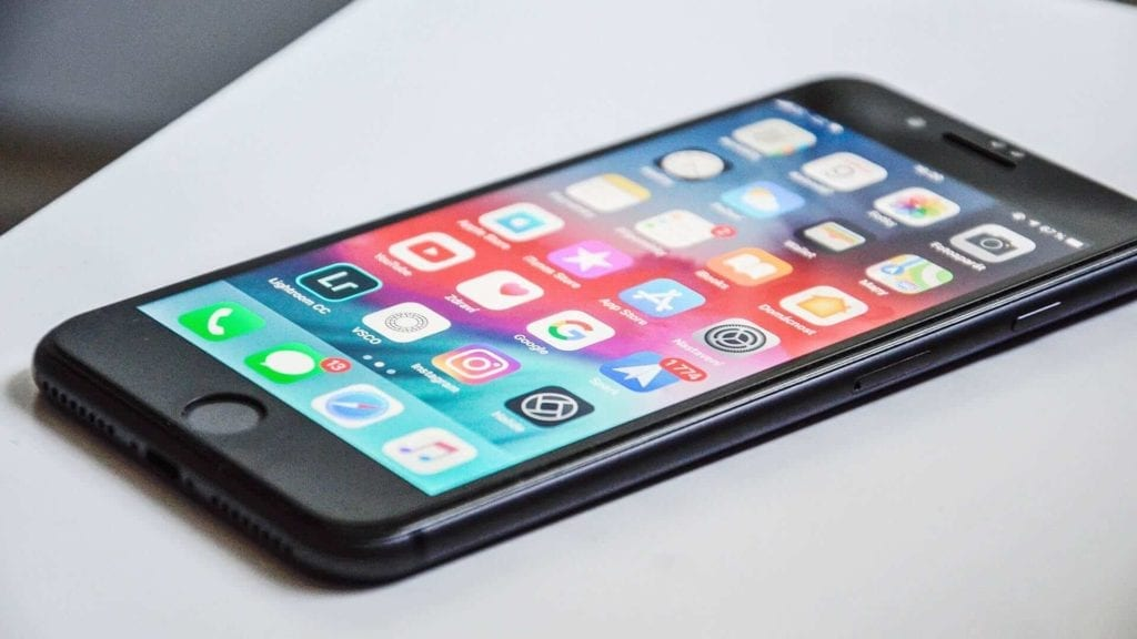 An iphone on a white table with applications shown on the screen