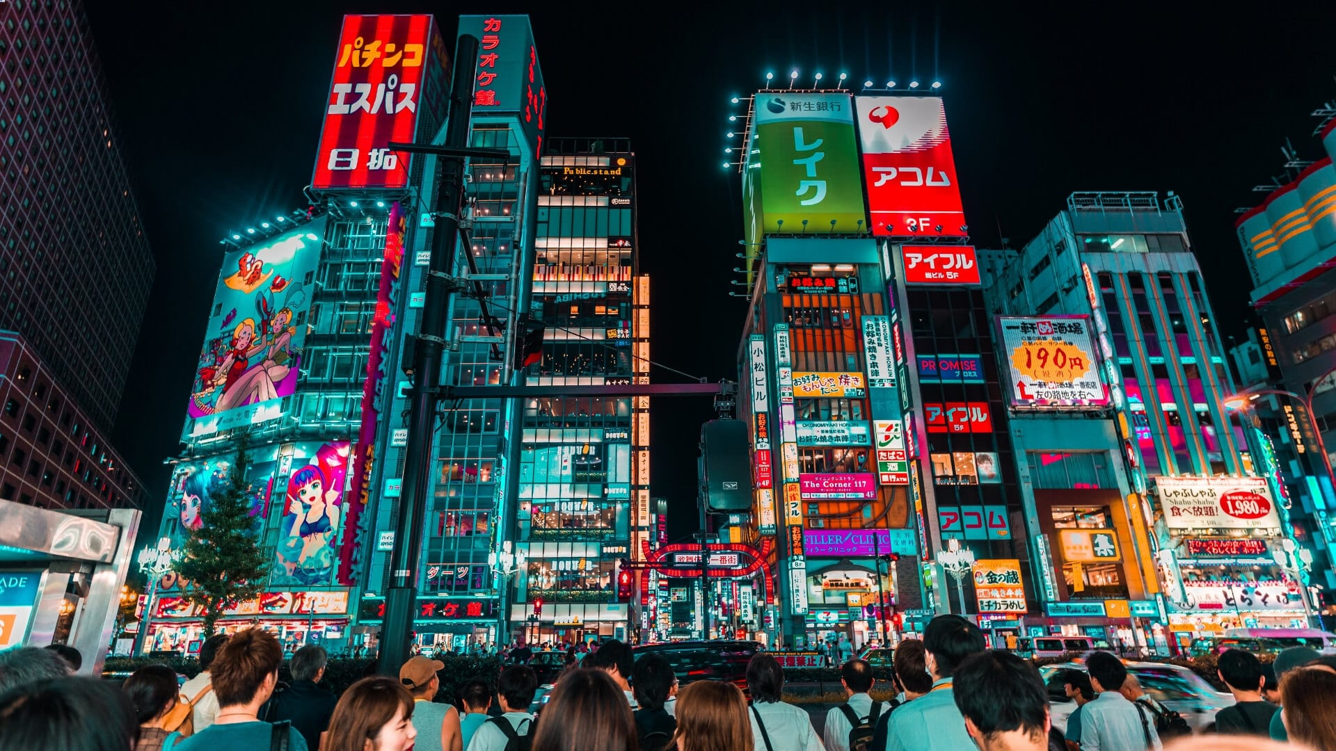 Many people are standing in front of high illuminated buildings in Tokyo.