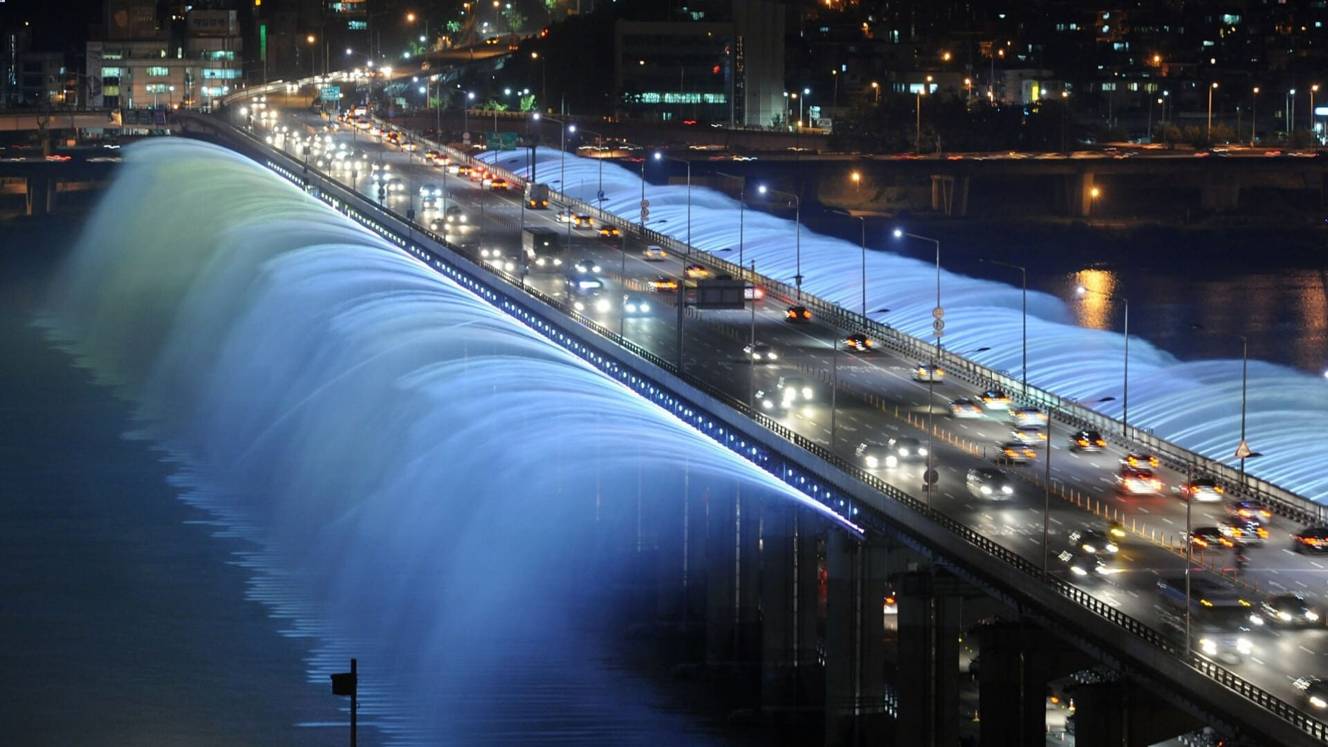Cars are driving over a bridge where water comes out during night in South Korea.
