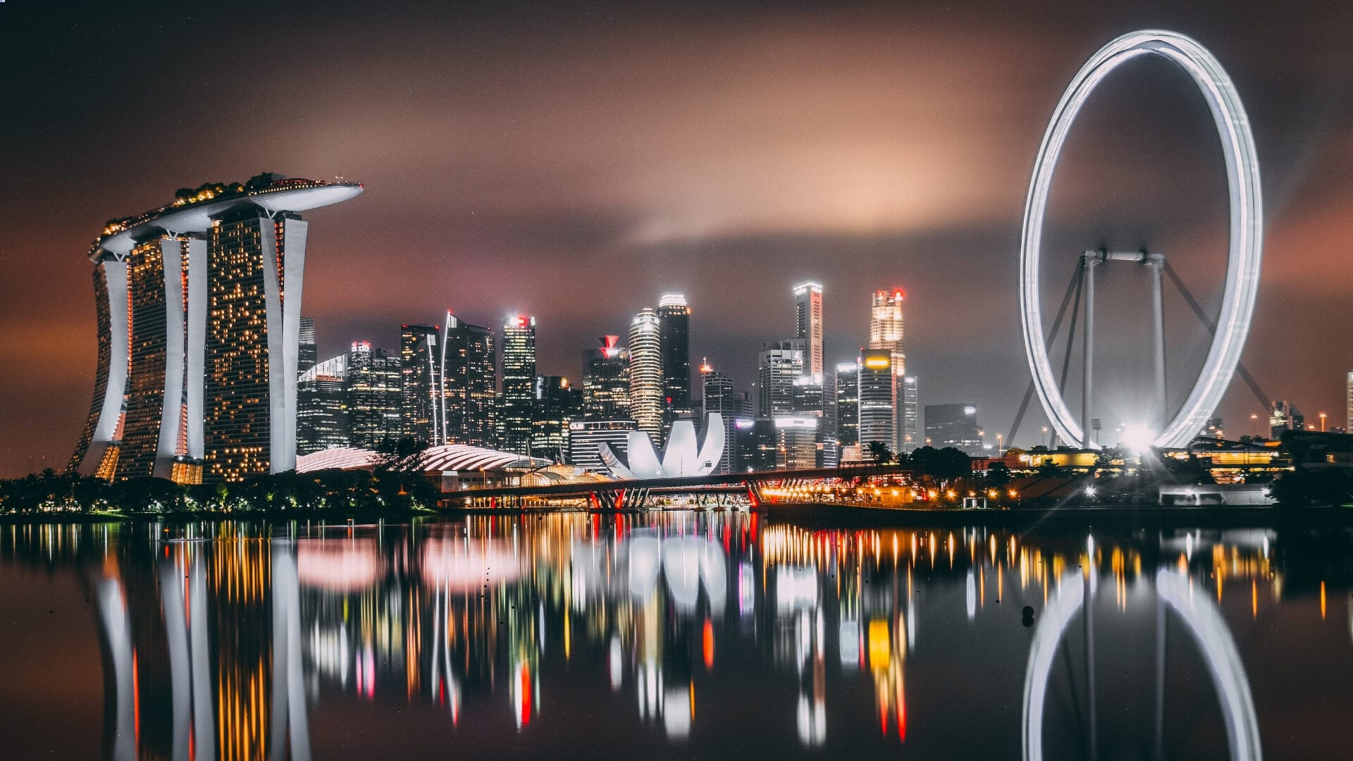 Illuminated high buildings are standing next to a bay during a night in Singapore.