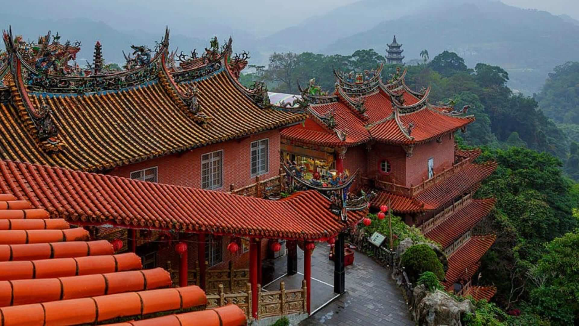 A red temple on a hill full of green trees in Taiwan.