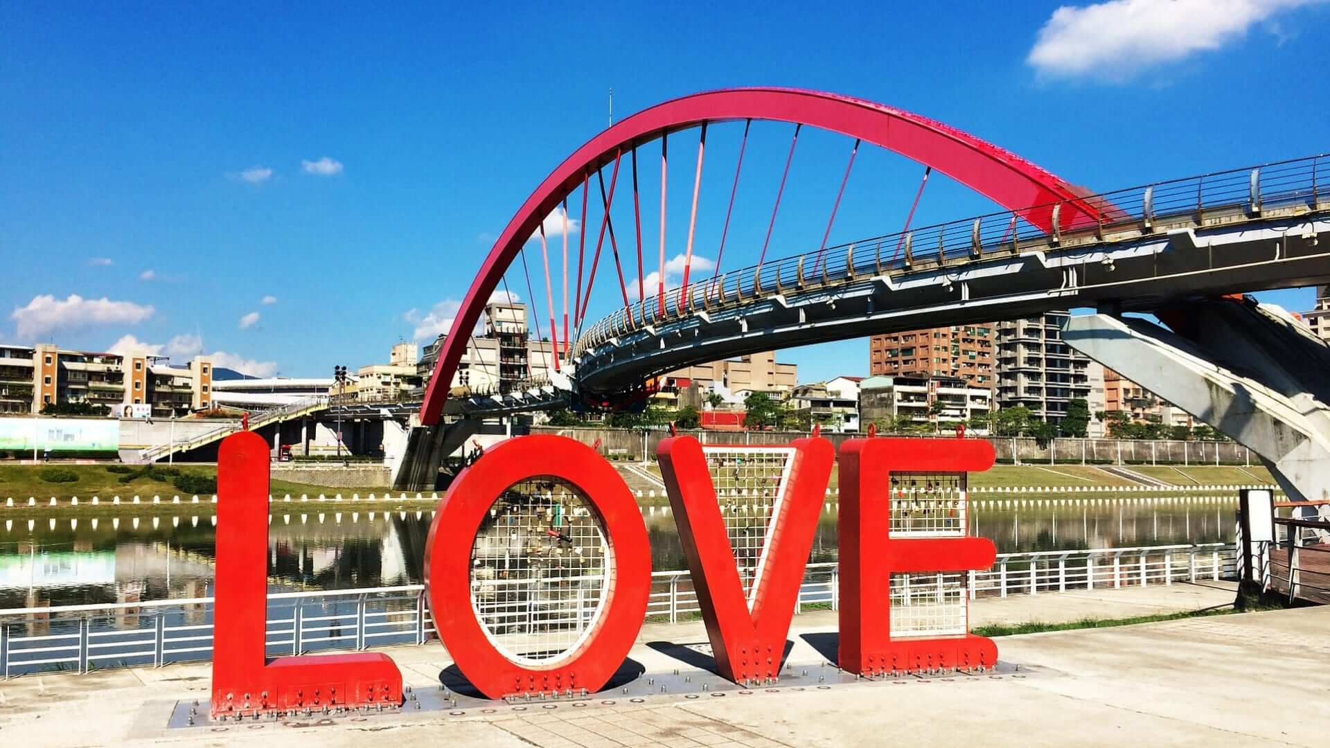 Red big letters that make the word LOVE are standing in front of a red bridge in Taiwan.