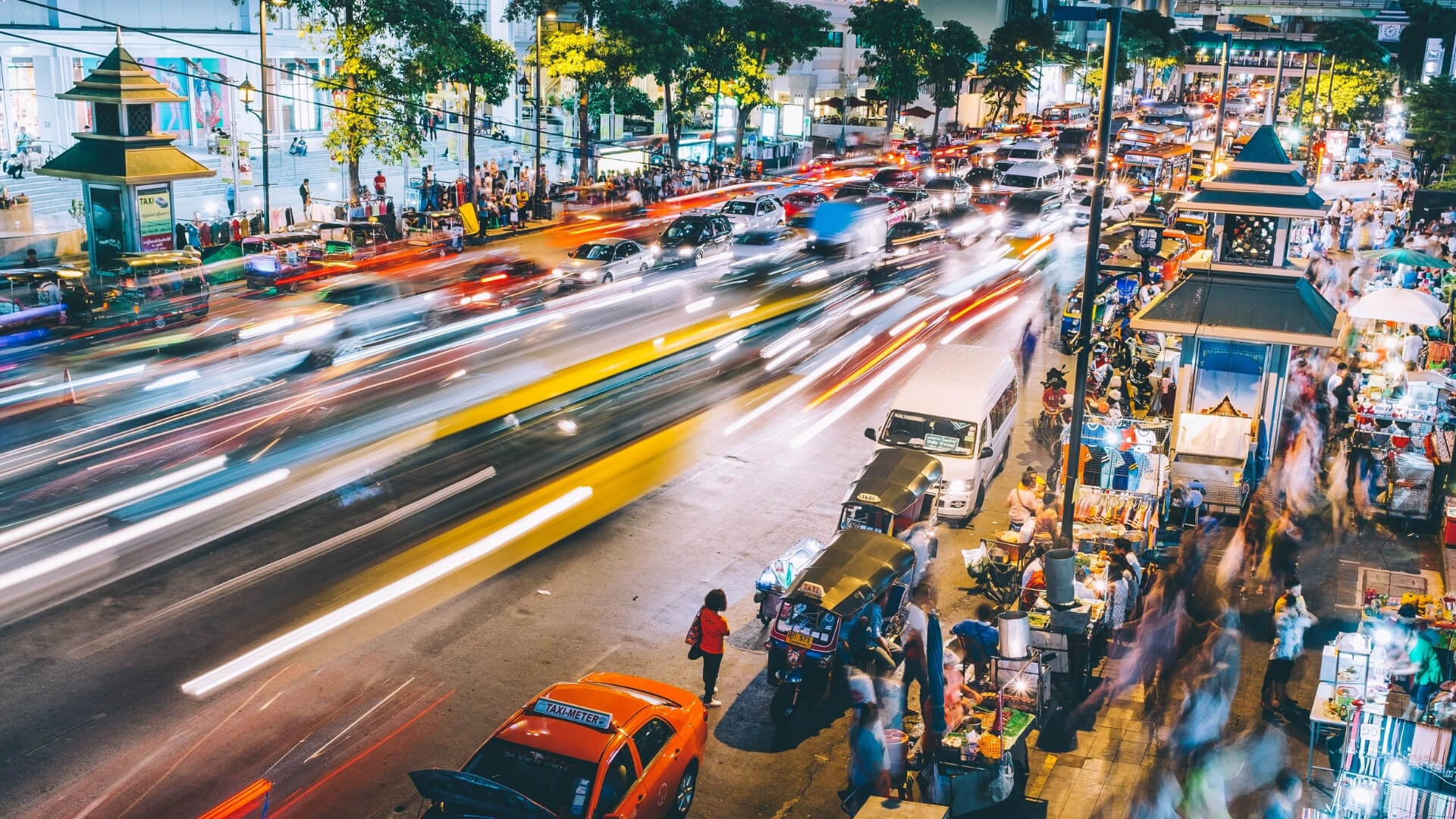 Cars are driving fast during a night in Bangkok.