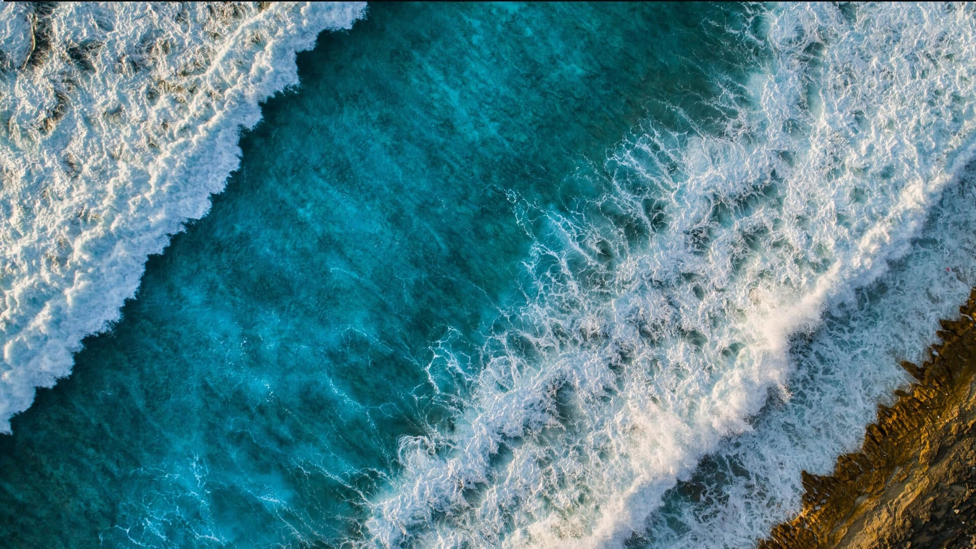 Waves in a bright blue ocean are washing ashore in Asia.