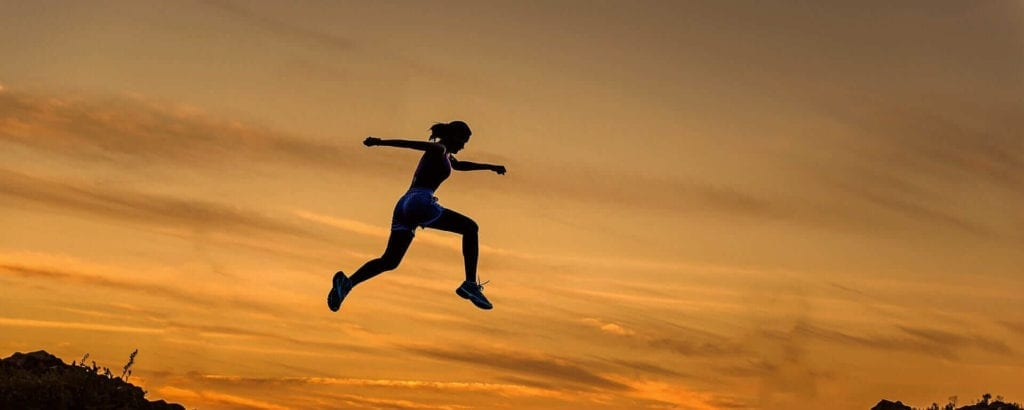 woman jumping in the air achieve your dreams