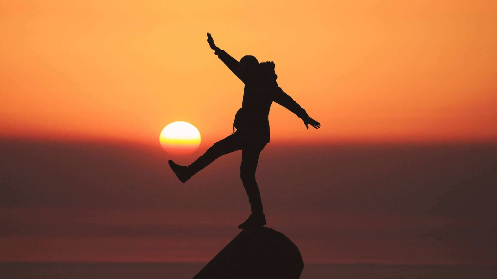 silhouette of a person standing on a rock
