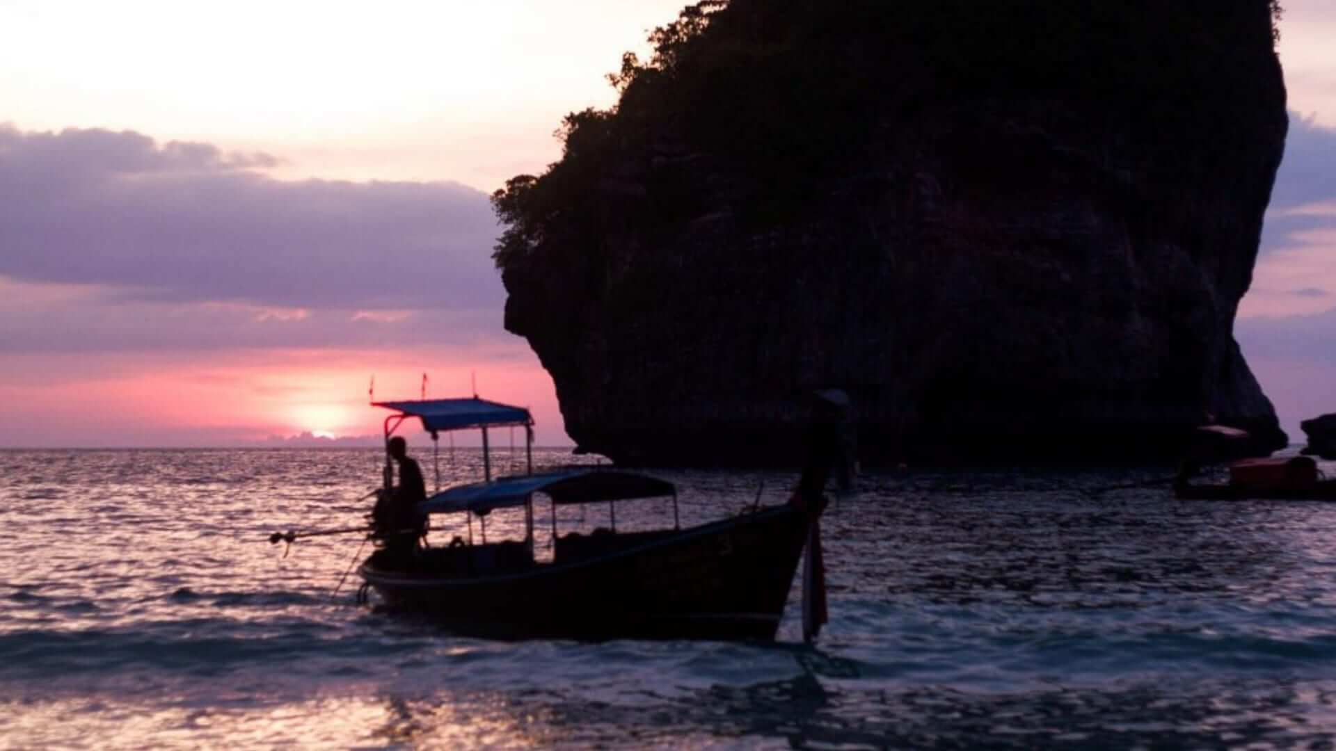 A man is fishing from a boat in front of the Phi Phi Islands during sunset in Thailand.