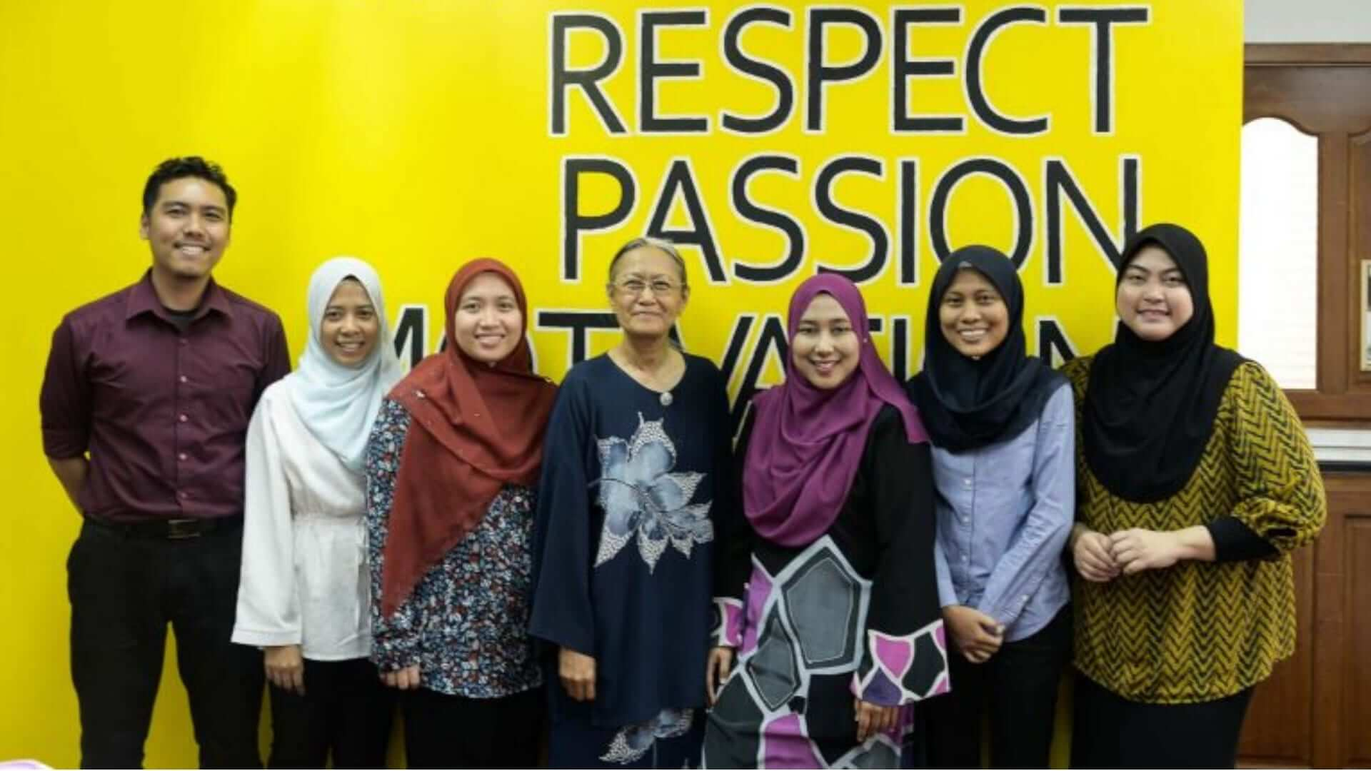 Malaysian women are standing in front of a yellow wall with the words respect and passion written on it at an university in Kuala Lumpur.