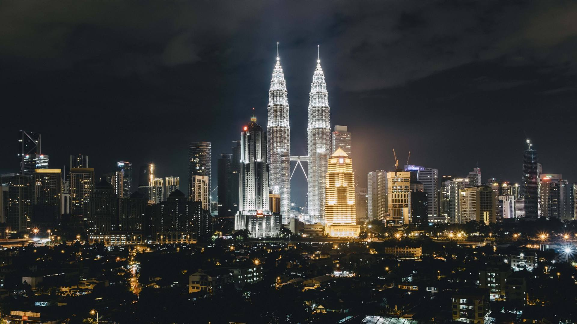 The Petronas Towers are illuminated and surrounded by other buildings during night in Kuala Lumpur.