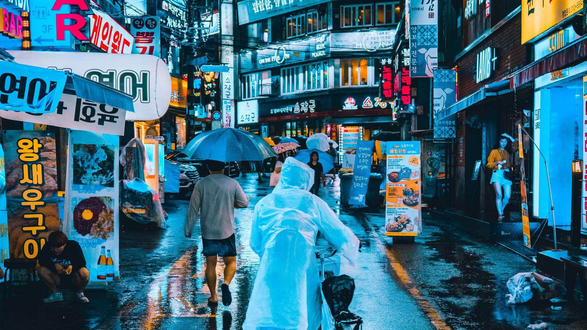 People walking with umbrellas during nighttime in Seoul.