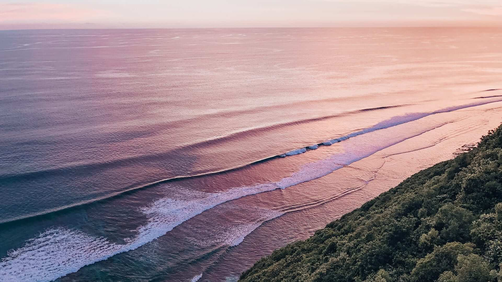 Waves breaking against the shore at sunset, trees and mountains in front