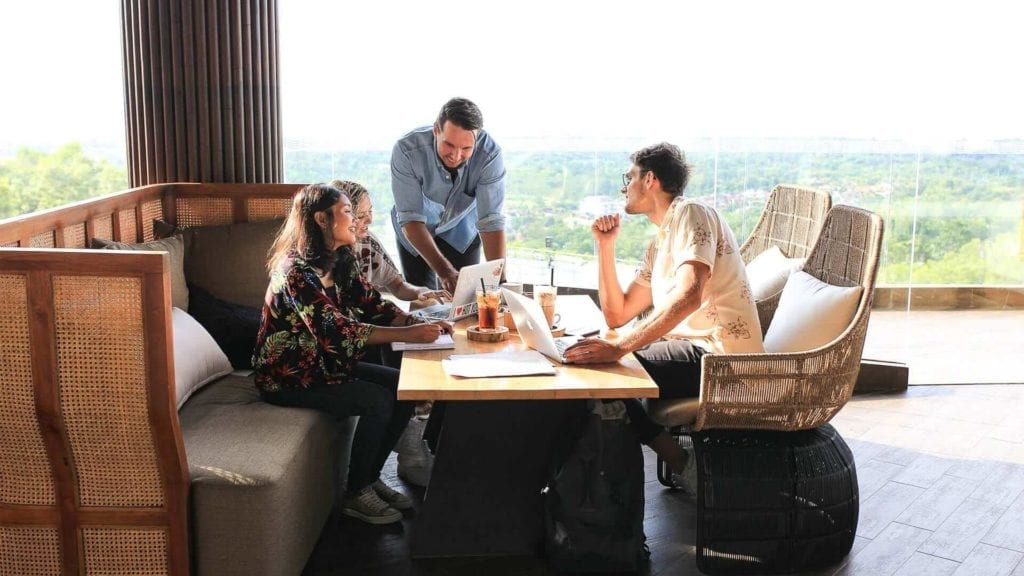 A group of people sit around a table with laptops and drinks while talking