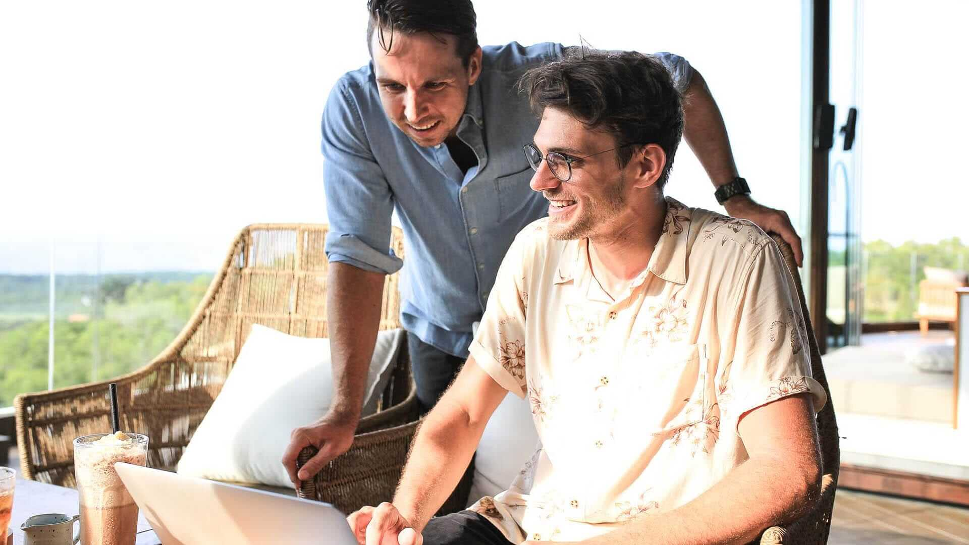 Two men are discussing while looking at a laptop
