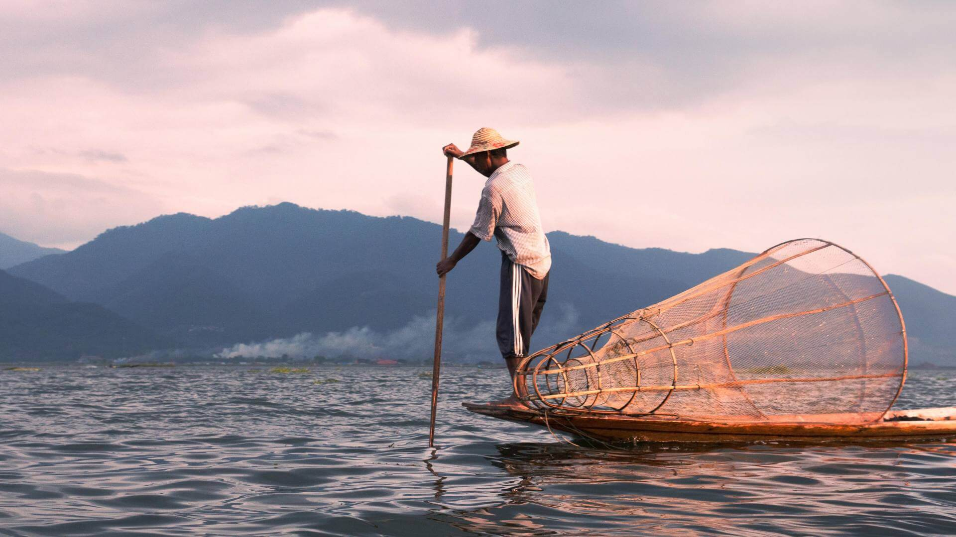 A man on a fishing boat with a straw hat