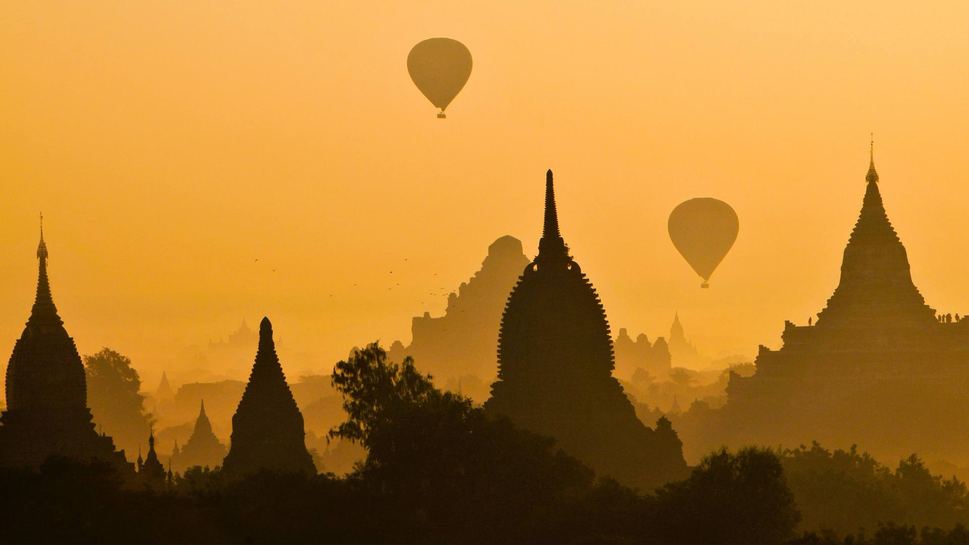 Silhouettes of temples and balloons