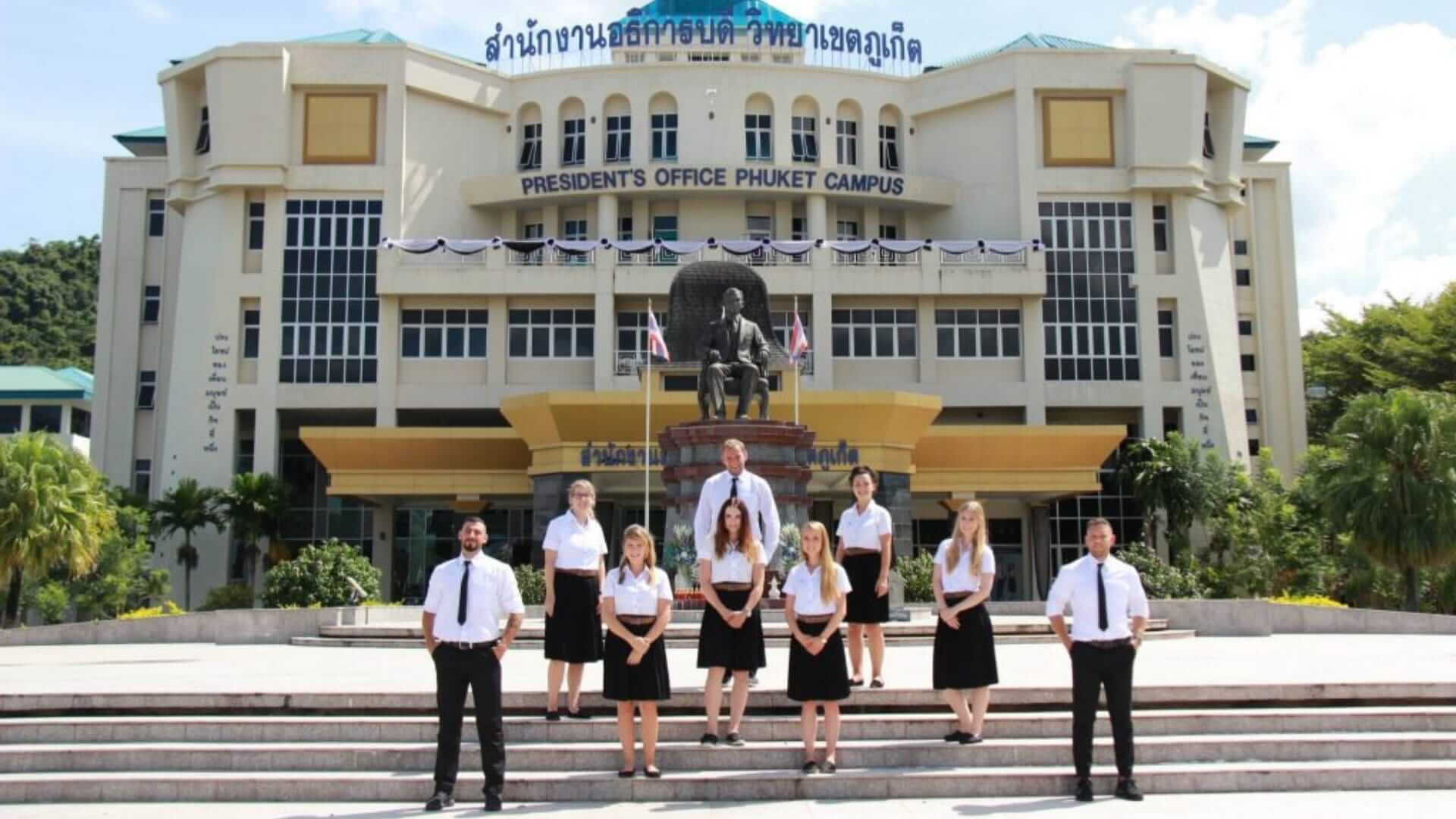 A group of people wearing business clothes are standing on the stairs in front of a university in Phuket.
