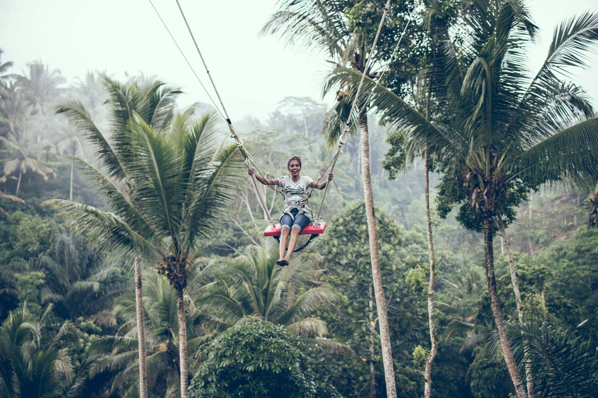 girl sitting in a swing in the middle of the jungle