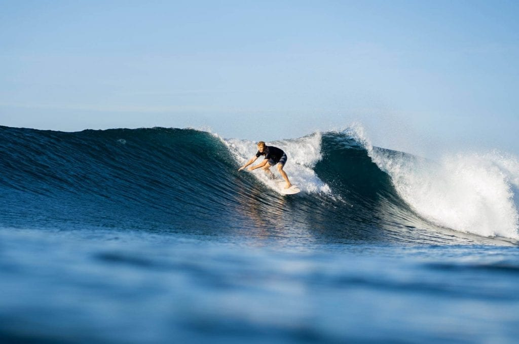 american student surfing in bali
