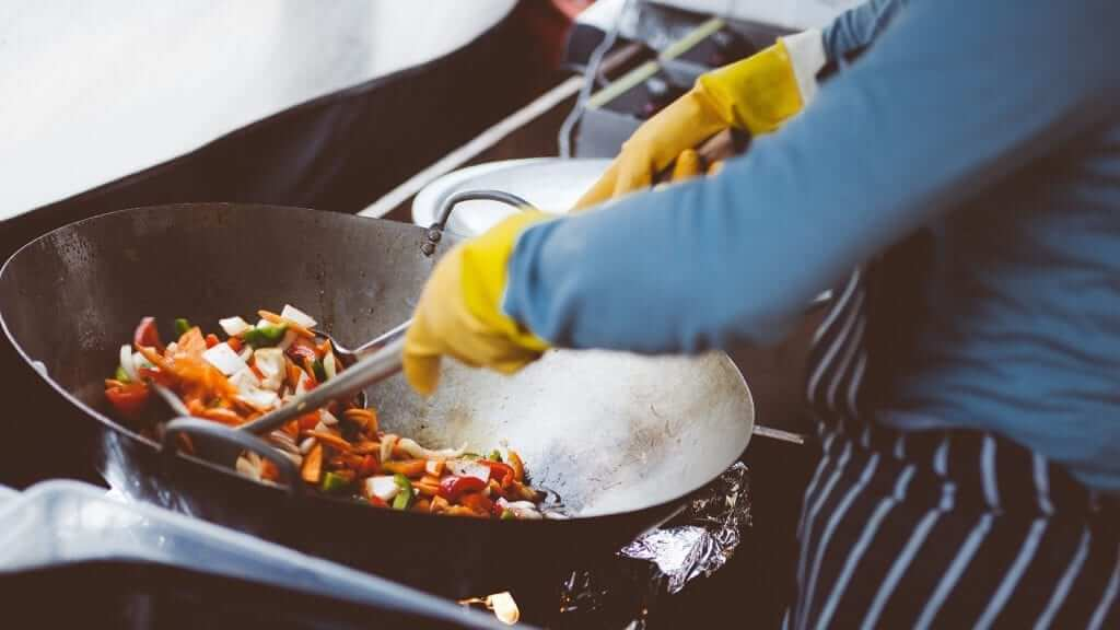 A person is cooking food in a big pan