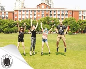 Four students jumping in the air on the Shanghai University campus area