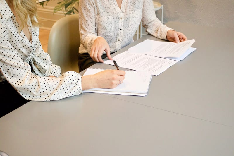 two woman doing paperwork