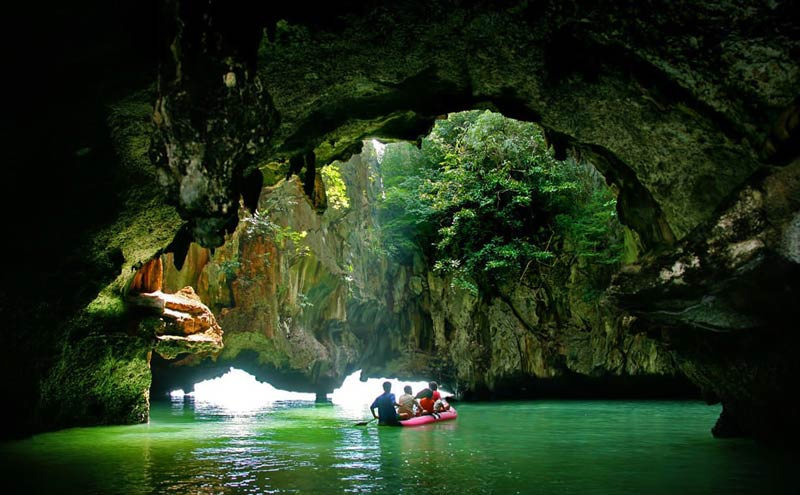 A red inflatable boat is leaving a cave in Phuket. 4 people are in the boat. The area outside the cave is tropical jungle