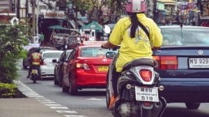 A woman in a yellow coat is driving a scooter in Thailand.