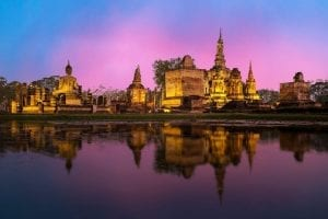 Water flows in front of the ruins of Ayutthaya as the sun sets painting the horizon purple