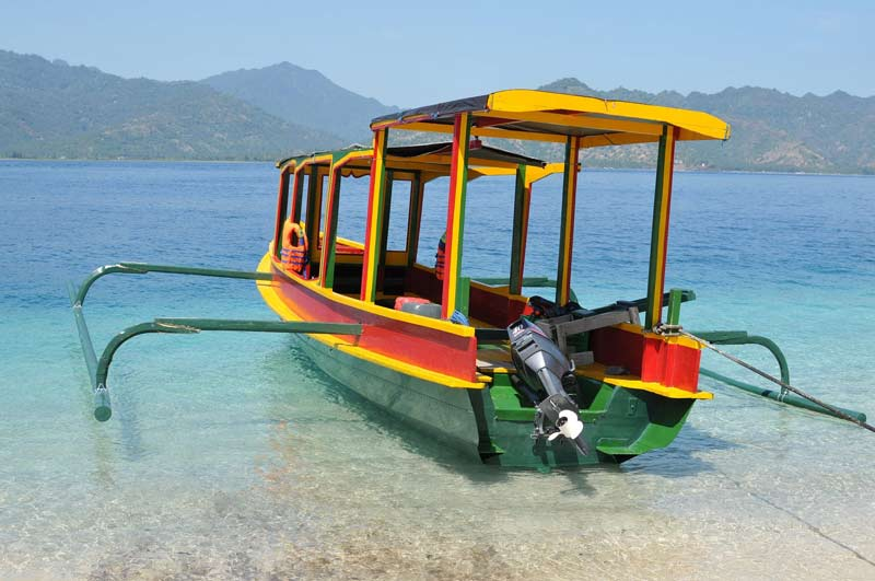 A open boat with yellow and red stripes is sitting in shallow, tropical water