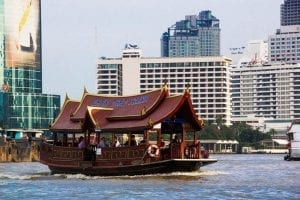 A river boat ferrying a crowd of tourists along the Chao Phraya river in Bangkok, Thailand