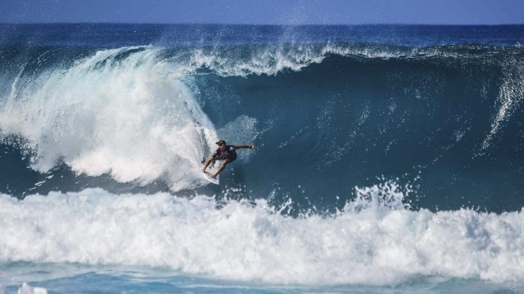 A blue wave crashes into foam behind as a surfer surfs the wave