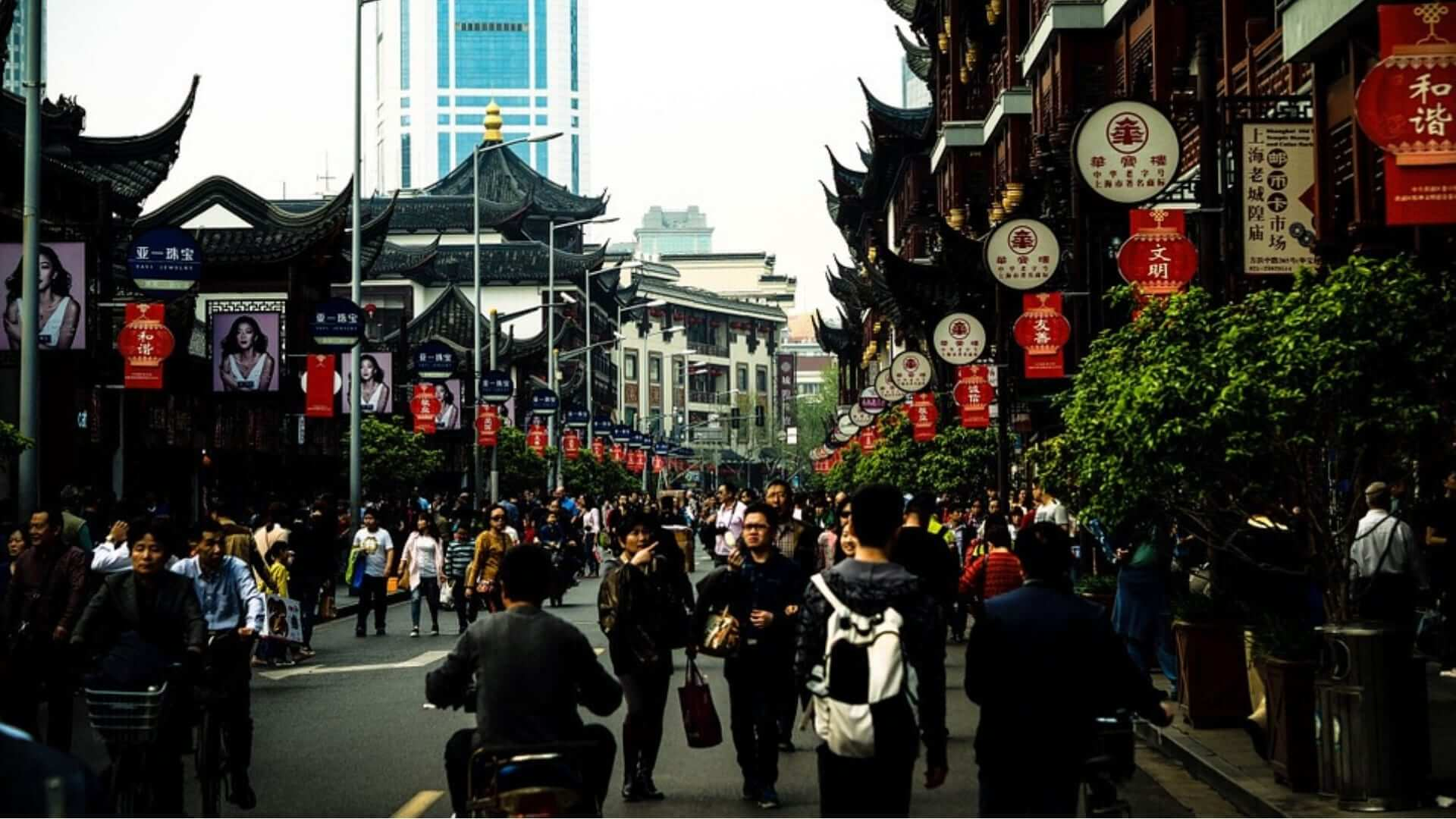People are walking in a street with old Chinese buildings in Shanghai.