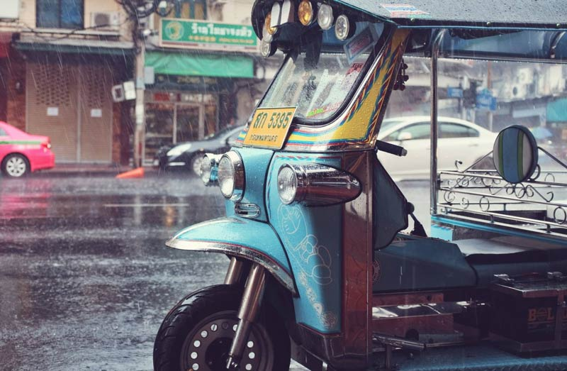 A blue tuk-tuk sits without a driver and the rain falls down in Thailand