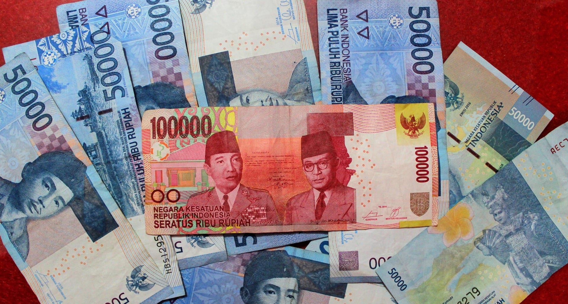Rupiah bills of multiple denominations are stacked on a table
