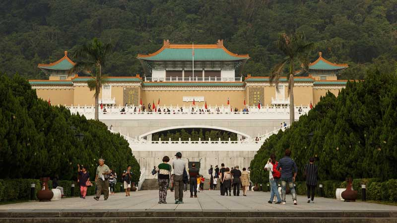 A palace is in the background with multiple Taiwanese flags. Tourists mingle in the walkway in the front and on the palace itself. Many have cameras out